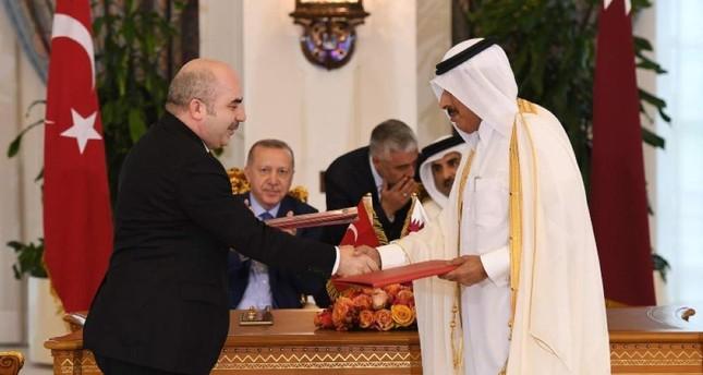 Turkish Central Bank Gov. Murat Uysal and Qatari counterpart Sheikh Abdulla Bin Saoud Al-Thani shake hands after signing a swap agreement on Nov. 25, 2019, in Doha, Qatar. (AA Photo)