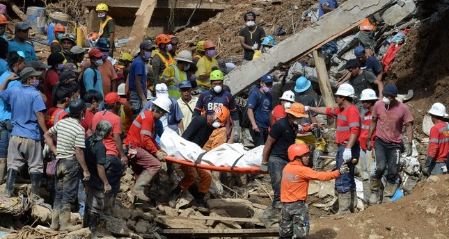 Rescuers carry a body bag containing a landslide victim, triggered by heavy rains during Typhoon Mangkhut, in Itogon, Benguet. (AFP Photo)