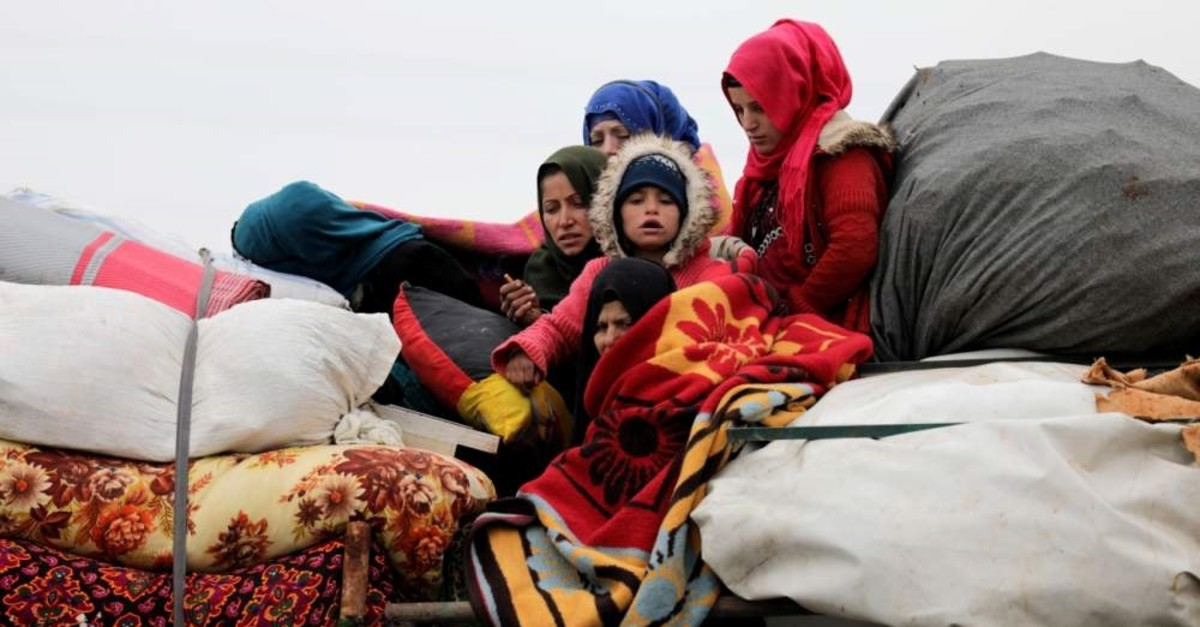 Internally displaced Syrians ride on a vehicle with their belongings in Hazano near Idlib, Syria, Feb. 11, 2020. (REUTERS Photo)