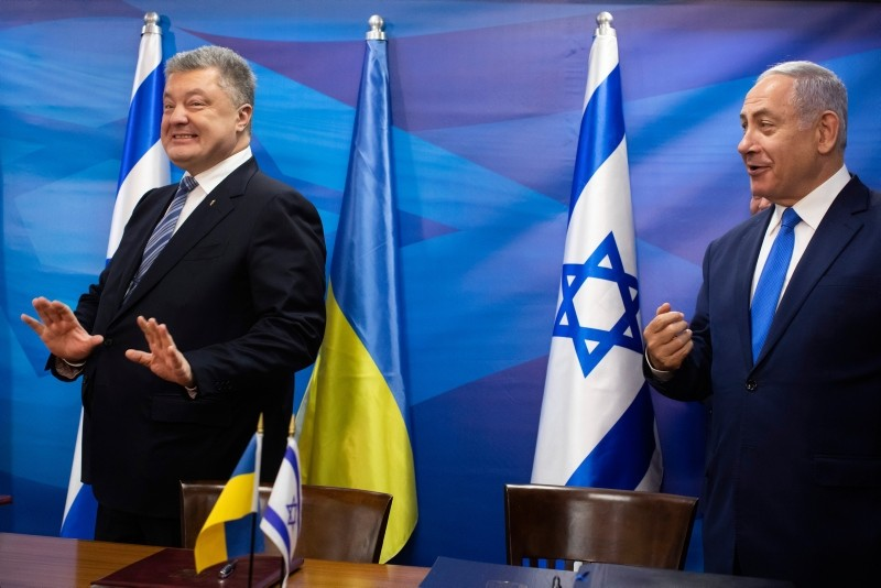 Ukraine President Petro Poroshenko, left, reacts with Israeli Prime Minister Benjamin Netanyahu after the signing of a free trade agreement by their trade ministers, in the Israeli Prime Minister's offices in Jerusalem, Jan. 21, 2019. (Pool via AP)