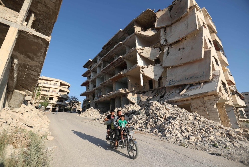 Syrian men ride a motorcycle past heavily-damaged buildings in Idlib province, Sept. 27.