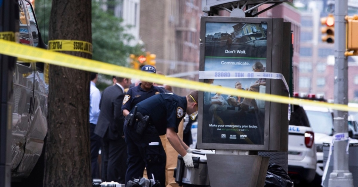 An investigator picks up a suspicious package that was thought to be an explosive device in Manhattan's Chelsea neighborhood Friday, Aug. 16, 2019 (AP Photo)