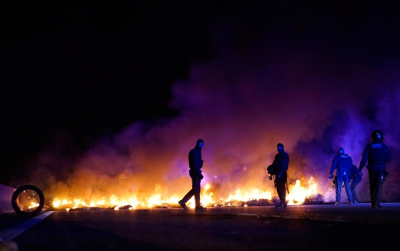 Police officers try to remove burning tires, set by demonstrators to block a highway in protest of the imprisonment of pro-independence political leaders during a general strike in Catalonia, Spain, Thursday, Feb. 21, 2019. (AP Photo)