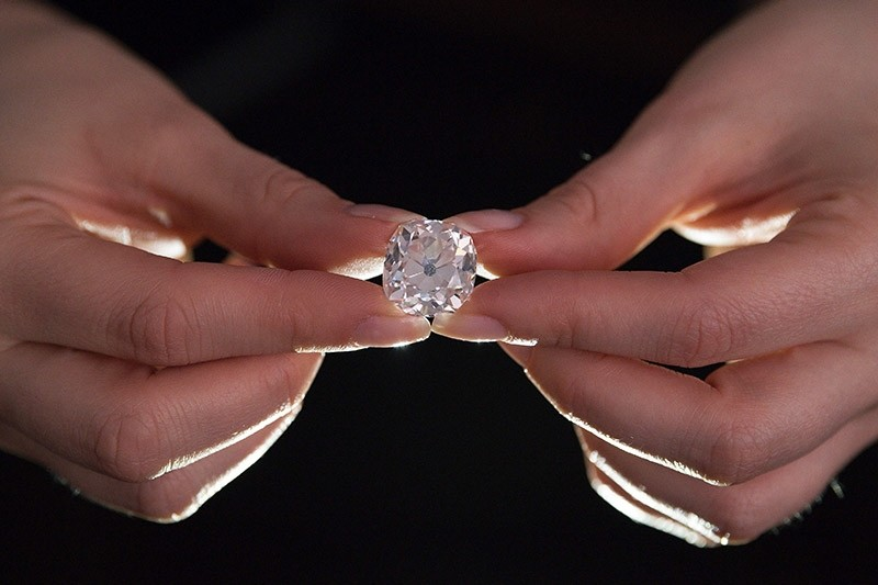 A member of Sotheby's staff poses holding a 26.27 carat, cushion-shaped, white diamond, for sale at Sotheby's auction house in London on May 22, 2017. (AFP Photo)