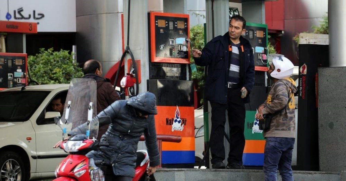 Iranians fill their vehicles at a petrol station in Tehran, on November 15, 2019. - Iran imposed petrol rationing and raised pump prices by 50 percent or more today, in a new move to cut costly subsidies that have fuelled high consumption and rampant smuggling. The Islamic republic provides some of the most heavily subsidised petrol in the world, with the pump price previously standing at just 10,000 rials (less than nine US cents) a litre. (Photo by STR / AFP)