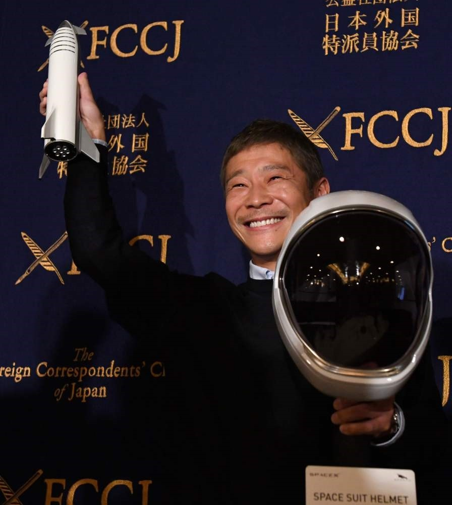 Yusaku Maezawa, entrepreneur and CEO of ZOZOTOWN and SpaceX BFR's first private passenger, poses with a miniature rocket and a space helmet prior to the start of a press conference at the Foreign Correspondents' Club of Japan in Tokyo on Oct. 9.