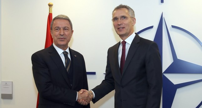 Defense Minister Hulusi Akar shakes hands with NATO Secretary-General Jens Stoltenberg during a NATO defense ministers meeting in Brussels, Feb. 13, 2019.