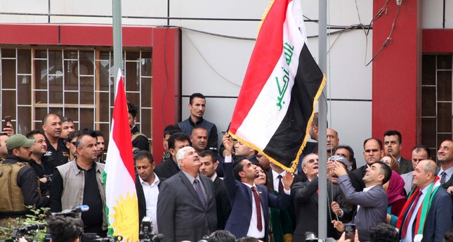 Kirkuk provincial governor raises the Iraqi flag to fly next to the Kurdish flag over a government building in Kirkuk on March 28, 2017. (AFP PHOTO)