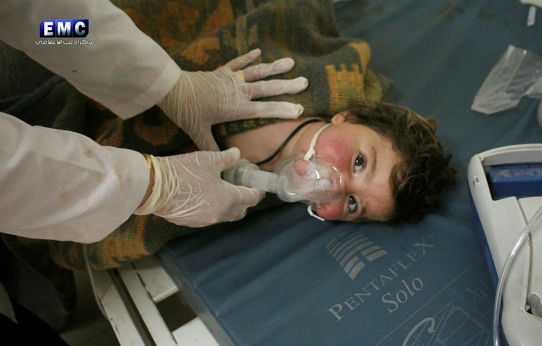 This photo provided by Edlib Media Center shows a Syrian doctor treating a child following a suspected chemical attack.