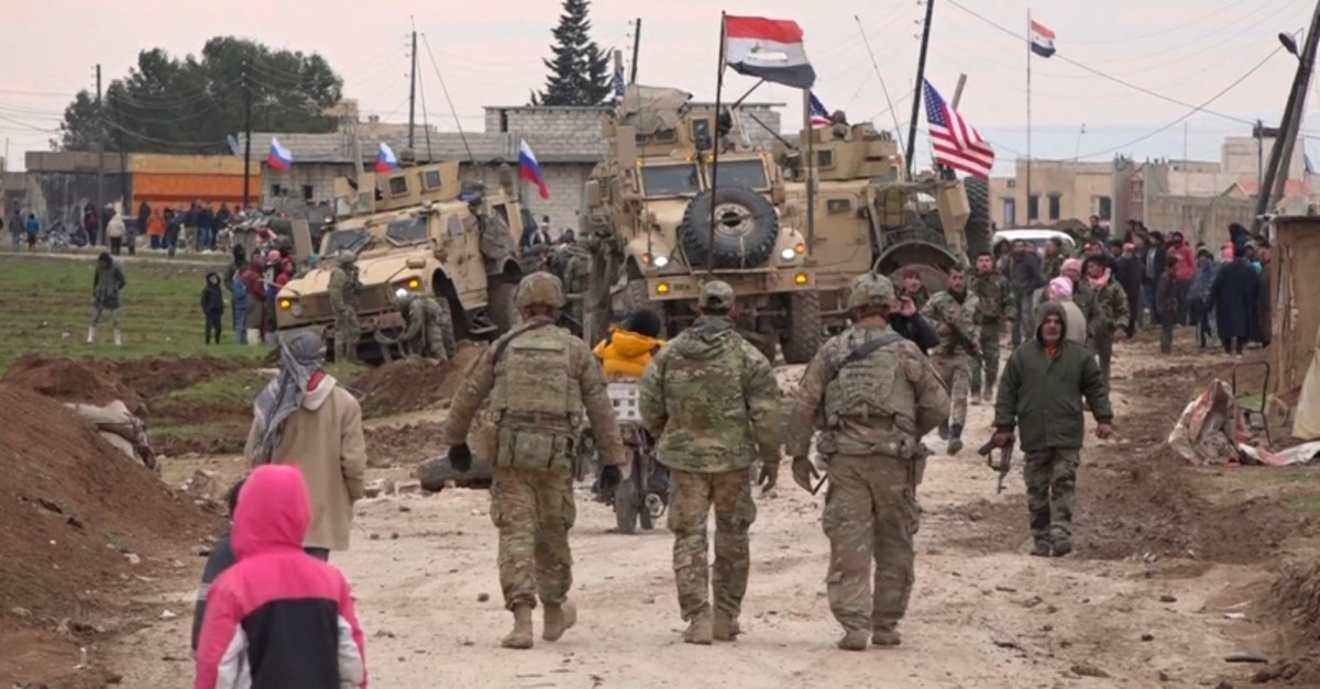 In this frame grab from video taken on Wednesday, Feb. 12, 2020, Russian, Syrian and others gather next to an American military convoy stuck in the village of Khirbet Ammo, east of Qamishli city, Syria, Wednesday, Feb. 12, 2020. (AP Photo)