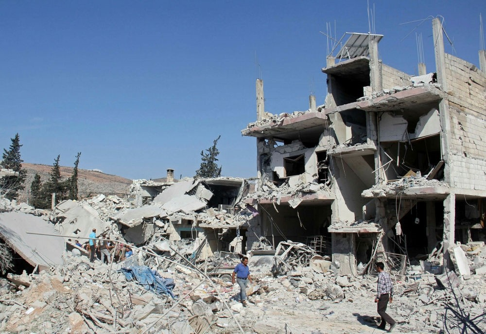 Residents search for survivors amid the rubble of a building following a reported overnight air strike in Idlib province near the Turkish border on Sept. 30.