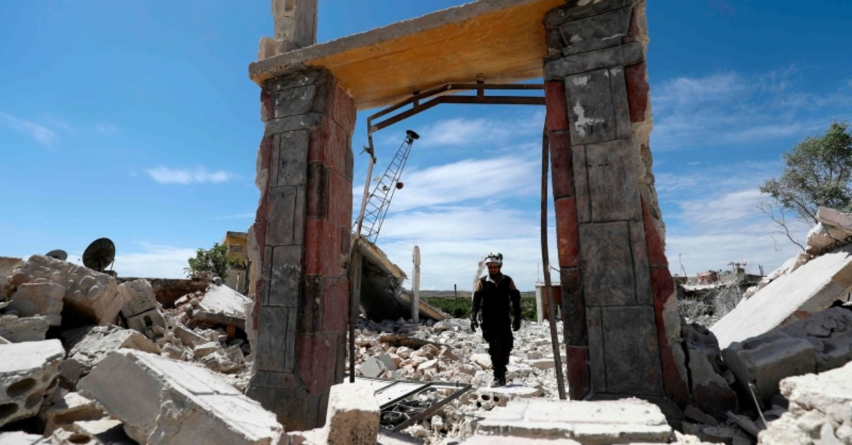 A member of the Syrian Civil Defence (White Helmets) inspects the rubble following shelling by Assad regime forces and their allies on a the village of Maarit Sin in the countryside of Idlib province on May 11, 2019. (AFP Photo)
