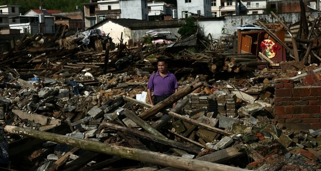 A villager stands on the debris of his house damaged by flood following heavy rainfall in Qingliu county, Sanming, Fujian province, China June 3, 2019. (Reuters Photo)