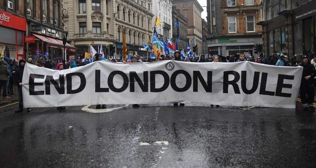 Pro-independence protesters hold up a long banner that reads End London Rule during a march organized by the grassroots organization, All Under One Banner calling for Scottish independence, Glasgow, Jan. 11, 2020. Thousands of independence supporters are expected the march through the streets of Glasgow, despite a rally that was planned to conclude the event being cancelled after Met Office warnings of high winds. Photo by ANDY BUCHANAN / AFP