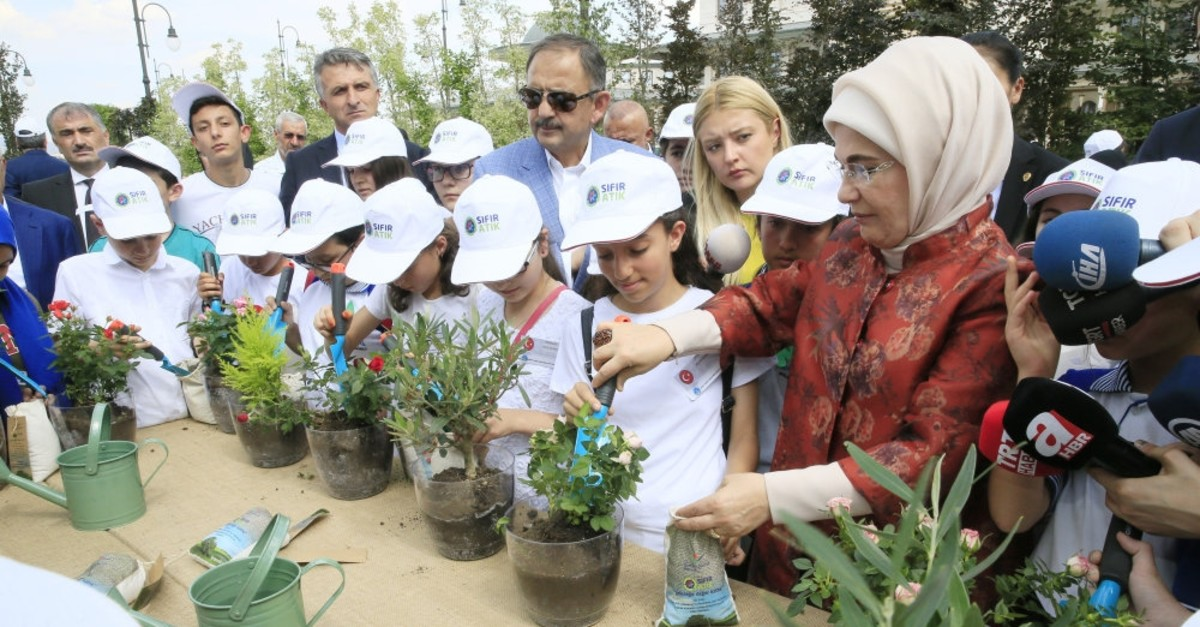 First lady Emine Erdou011fan and children pour compost from recycled materials into flower pots, June 5, 2019.