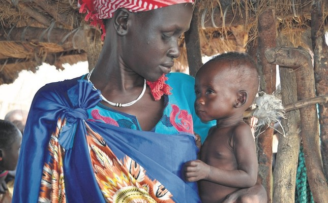 A woman holds her severely malnourished 10-month old daughter at the feeding center for children, South Sudan, Dec. 10, 2017.
