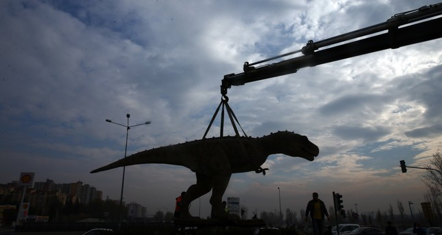A crane hoists the dinosaur statue.