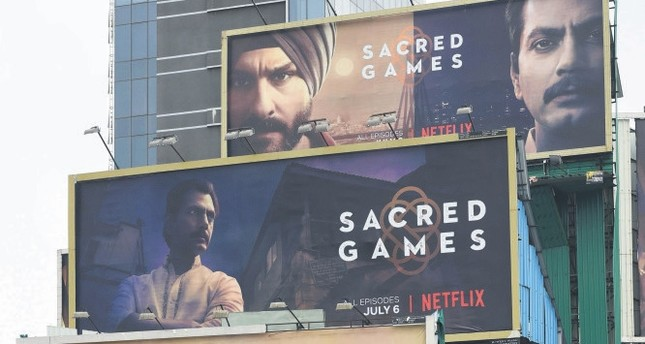 Indian commuters travel past large billboards for 'Sacred Games,' the upcoming Indian series on Netflix, in Mumbai.