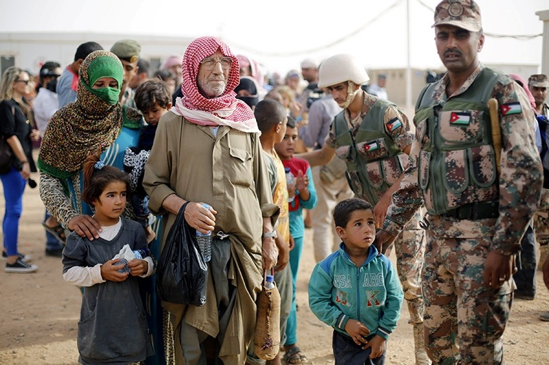 Syrian refugees wait to board a Jordanian army vehicle after crossing into Jordanian territory with their families, in Al Ruqban border area, near the northeastern Jordanian border with Syria on Sept. 10, 2015. (Reuters Photo)