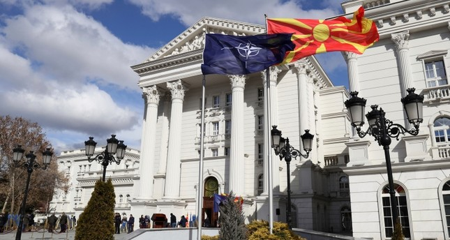 Macedonian, right, and NATO flag wave in front of the government building during a ceremony in Skopje, Tuesday, Feb. 12, 2019. (AP Photo)