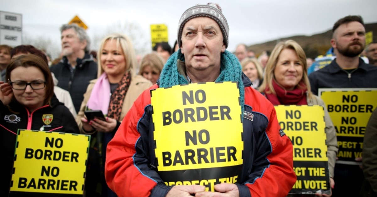 In this file photo taken on March 30, 2019, protesters hold placards at the Carrickcarnan border between Newry in Northern Ireland and Dundalk in the Irish Republic on March 30, 2019. (AFP Photo)