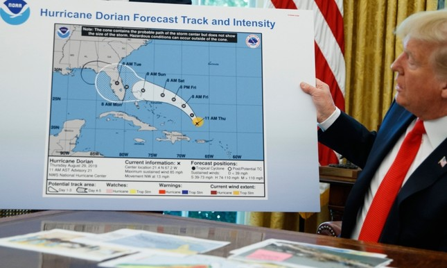 U.S. President Donald Trump holds a chart as he talks with reporters after receiving a briefing on Hurricane Dorian in the Oval Office of the White House, Wednesday, Sept. 4, 2019, in Washington. AP Photo