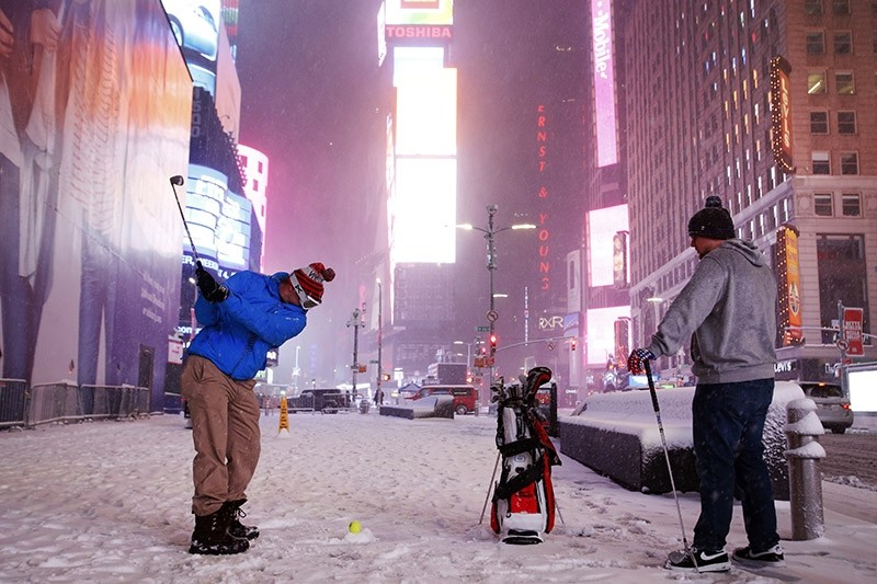 Two men play golf with a tennis ball as a snowstorm sweeps through Times Square, Tuesday, March 14, 2017, in New York. (AP Photo)