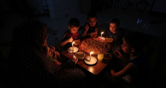A palestinian family eats dinner by candlelight at their makeshift home in the Rafah refugee camp, in the southern Gaza Strip, during a power outage on June 11, 2017. (AFP PHOTO)