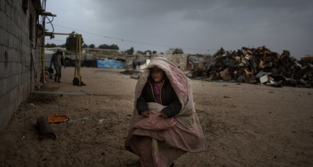 A Palestinian boy warms himself with a blanket, southern Gaza Strip, January 8, 2019.