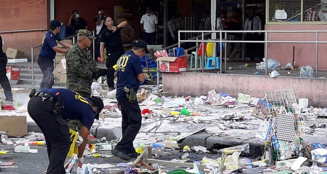 Members of the Philippine National Police (PNP) Scene of the Crime Operatives (SOCO) gather evidences on the site of an explosion on New Year's Eve outside a shopping mall in Cotabato City, southern Philippines, 31 December 2018. (EPA Photo)