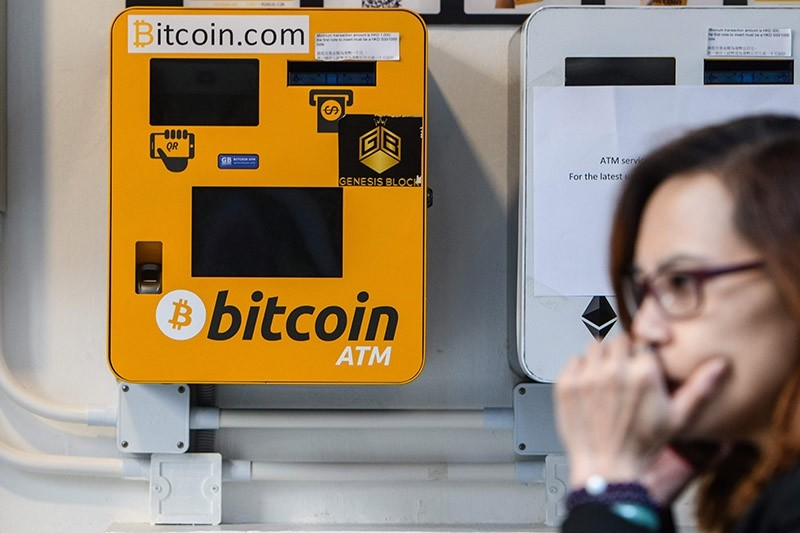 A woman uses her phone as she walks past an ATM machine for digital currency Bitcoin in Hong Kong on December 18, 2017. (AFP Photo)