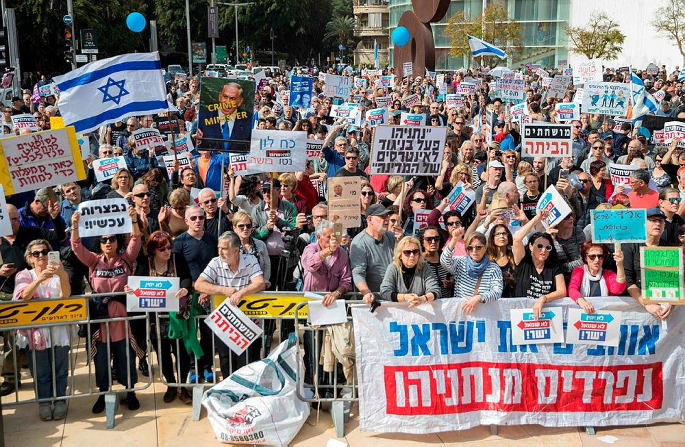 Israeli protesters raise signs as they demonstrate against Prime Minister Benjamin Netanyahu in the wake of police recommendations to indict corruption, in the coastal city of Tel Aviv on February 16, 2018. (AFP PHOTO)