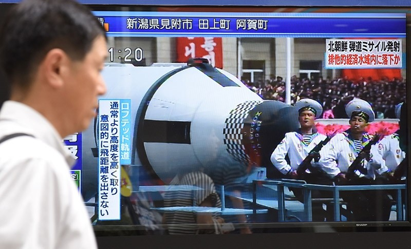 A pedestrian walks past a screen in Tokyo on July 4, 2017 broadcasting file news footage of a military parade showing North Korean soldiers and a missile, after a ballistic missile was launched by North Korea earlier in the day. (AFP Photo)