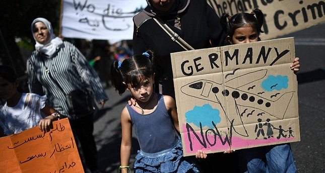 Two children hold a placard picturing a plane as they take part in a demonstration in central Athens outside the German embassy to protest against the limitation of reunification of families in Germany, on August 2, 2017. (AFP Photo)