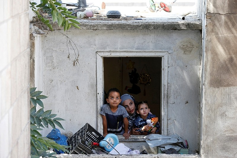 27-year-old Syrian refugee Alaa Masalmeh and her children, 5-year-old Samer and 3-year-old Mieral, look out of their home's window in Amman, Jordan, Aug. 1, 2018. (Reuters Photo)