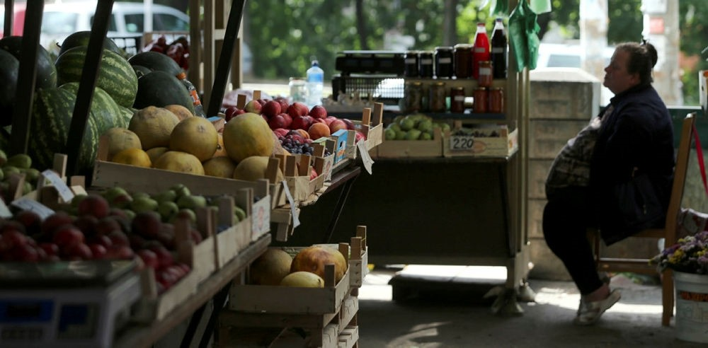 A woman who fruits seller awaits customers in an empty market in the suburbs of Belgrade, Serbia, 25 July 2017. (EPA Photo)