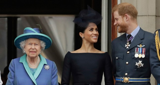 In this Tuesday, July 10, 2018 file photo Britain's Queen Elizabeth II, and Meghan the Duchess of Sussex and Prince Harry watch a flypast of Royal Air Force aircraft pass over Buckingham Palace in London. AP Photo
