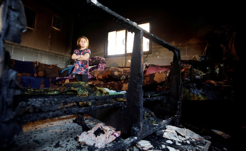 A girl looks at the damage inside the house of Palestinian Dawabsheh family after it was torched in the village of Duma near Nablus, in the occupied West Bank May 11, 2018. (Reuters Photo)