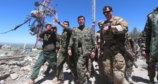 A U.S. military commander (R) walks with a commander (C) from the Kurdish People's Protection Units (YPG) as they inspect the damage at YPG headquarters after it was hit by Turkish airstrikes in Mount Karachok near Malikiya, Syria. (Reuters Photo)