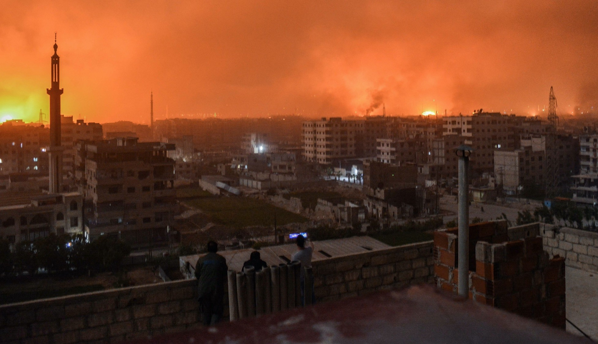 People stand on a roof to observe explosions on the horizon during regime strikes, in a southern district of the Syrian capital Damascus, April 28.