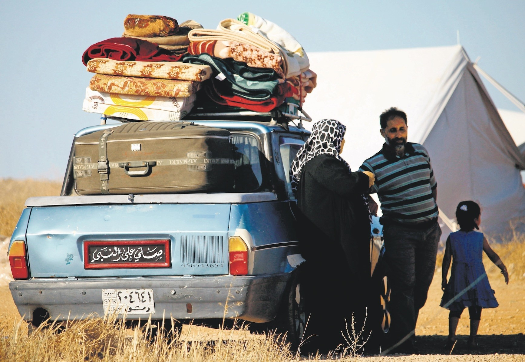 Displaced Syrians from Syriau2019s Daraa province fleeing shelling by pro-government forces wait in a makeshift camp to cross the Jordanian border.