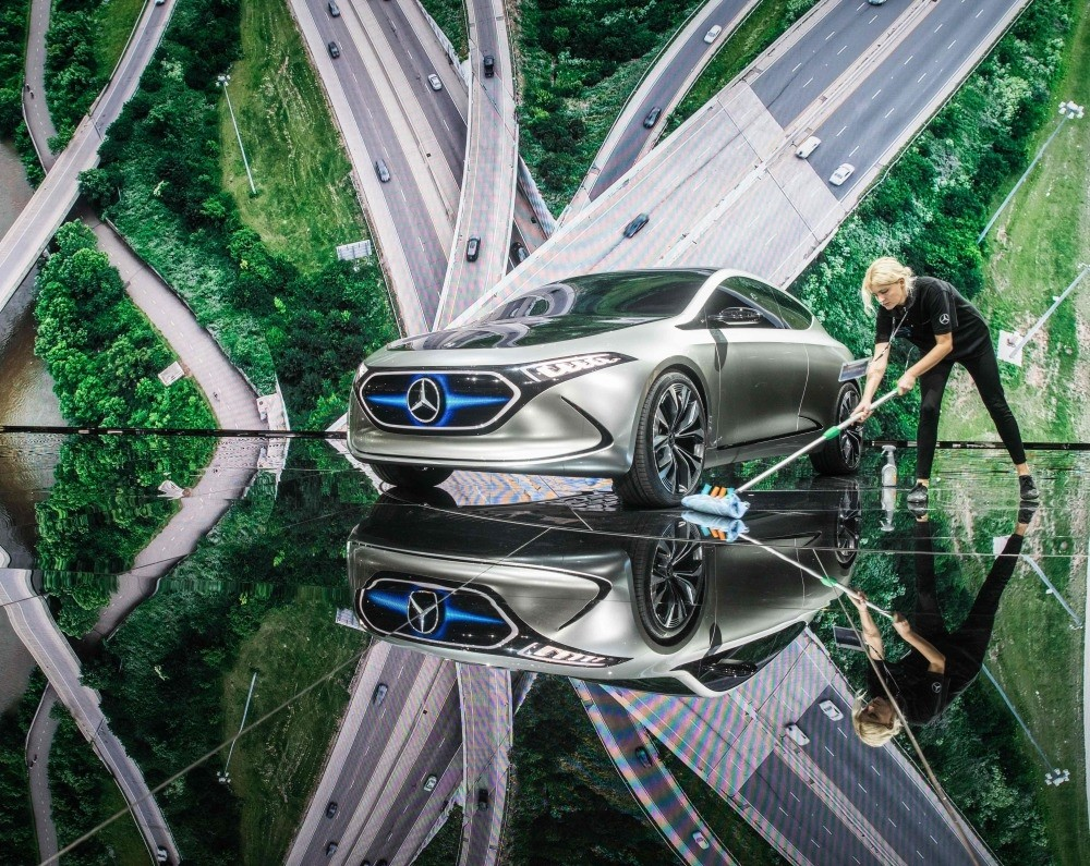 An employee cleans around electric concept car EQ A in Mercedes booth at the Internationale Automobil Ausstellung (IAA) auto show in Frankfurt am Main.