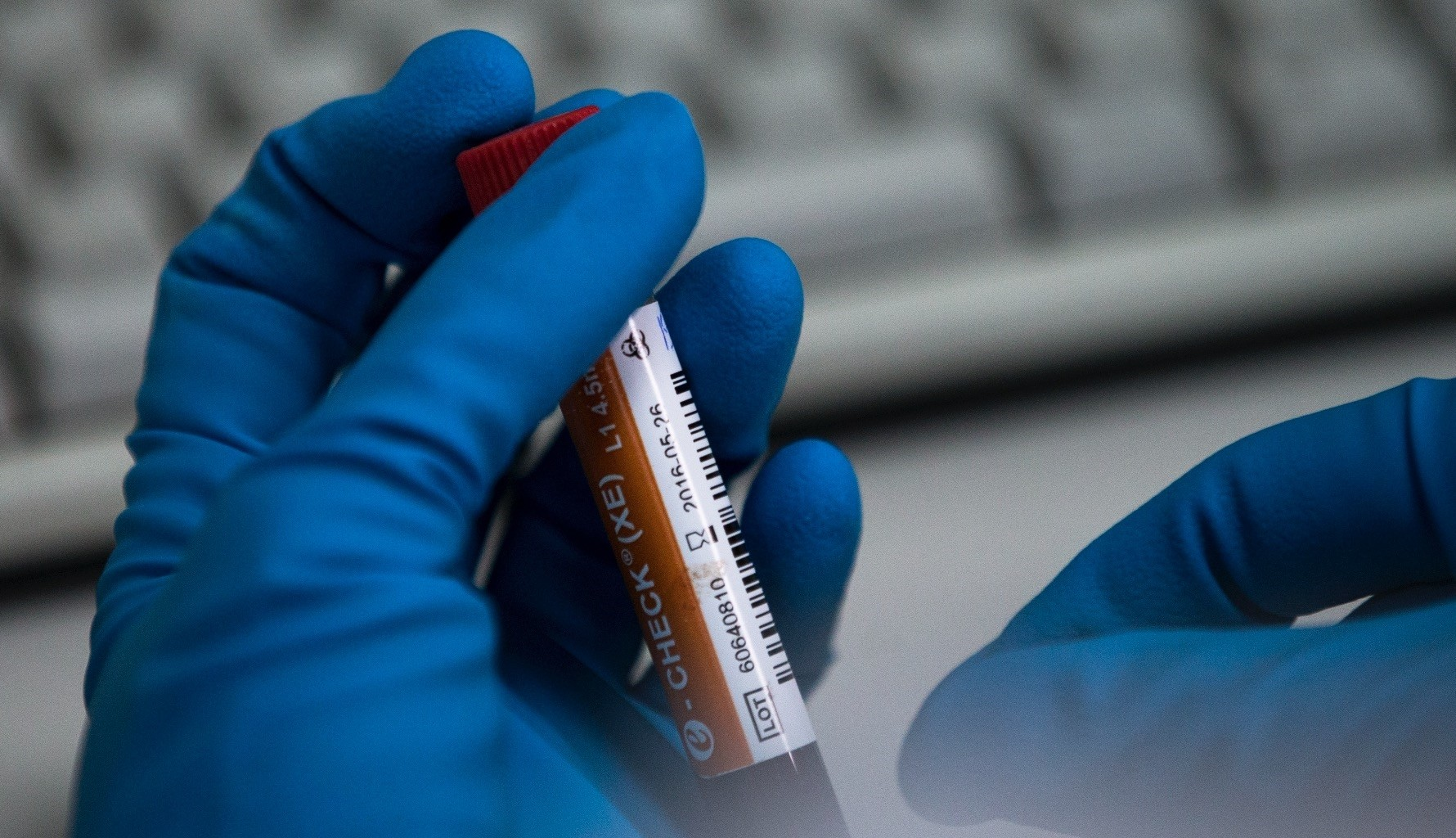 An employee of Russia's national drug-testing laboratory holds a vial in Moscow.