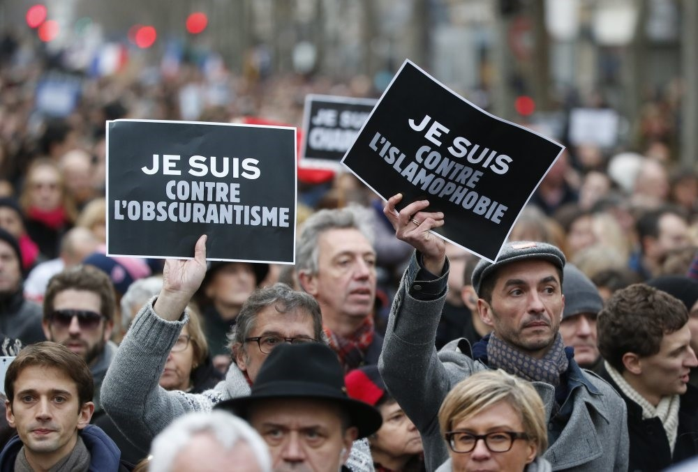 Demonstrators hold posters reading ,I am against obscurantism, (L) and ,I am against Islamophobia, during a march in Paris following a bloody attack by Daesh members in the French capital that killed 17, Jan. 11, 2015.