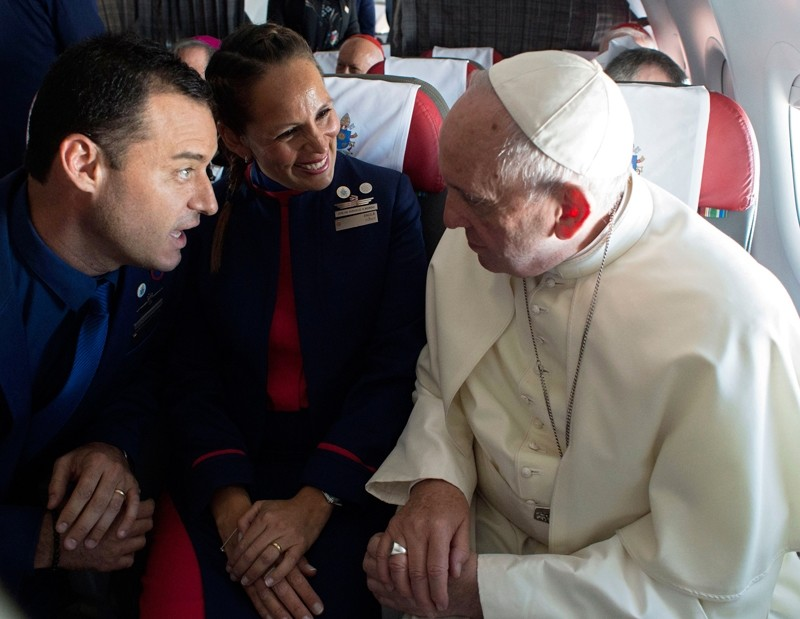 Handout picture released by the Vatican press office Osservatore Romano showing Pope Francis (R) taking to Latam airline flight attendants Paula Podest (C) and Carlos Ciuffardi on the plane, after marrying them (AFP Photo)