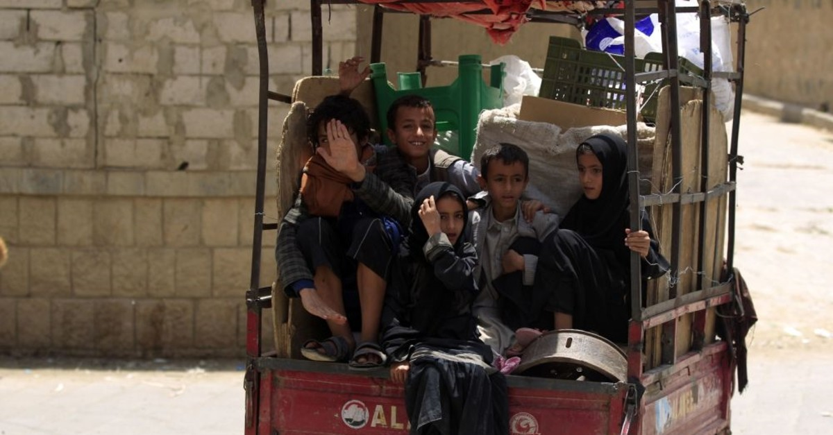 Children are transported in the back of a small truck in the province of Amran, Yemen, July 6, 2019.