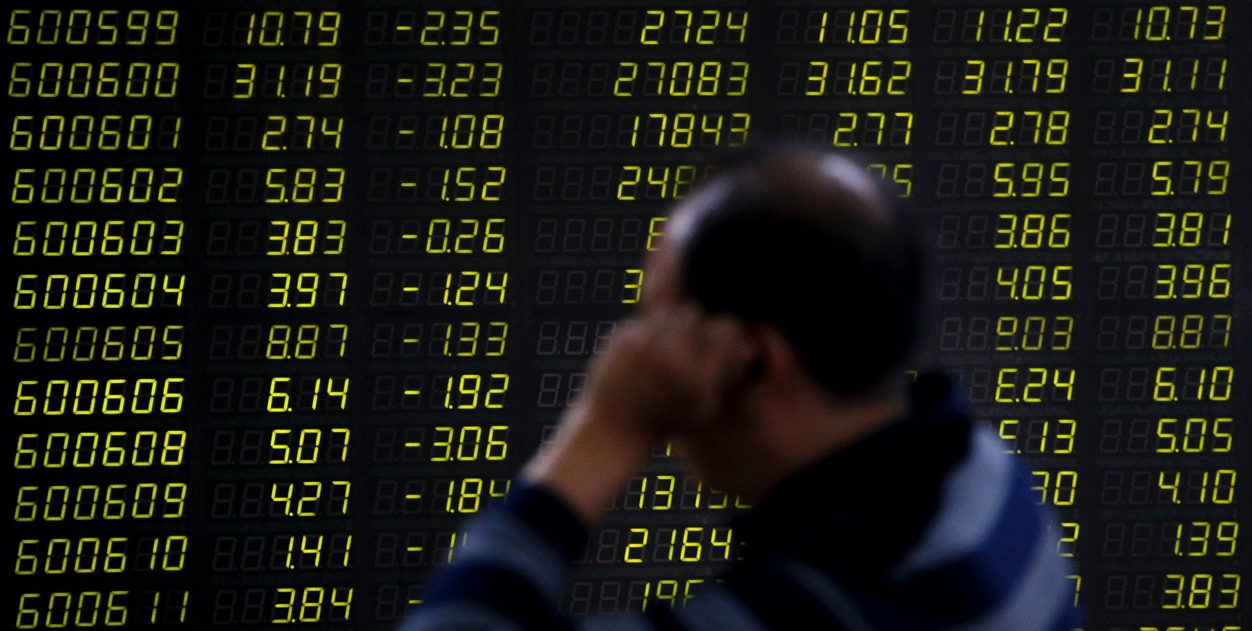 An investor sits in front of an electronic board displaying stock prices at a brokerage house in Beijing.