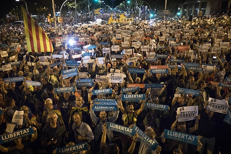 Holding signs reading in Catalan 'freedom', people gather to protest against the National Court's decision to imprison civil society leaders without bail, in Barcelona, Spain, Tuesday, Oct. 17, 2017. (AP Photo)