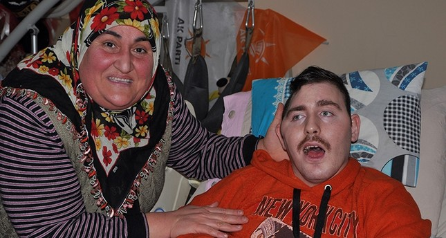 Gülsüm Kabadayı (left) smiles in a photo with paralyzed Russian boy she named Umut and had been taking care of since 2008 (IHA File Photo)