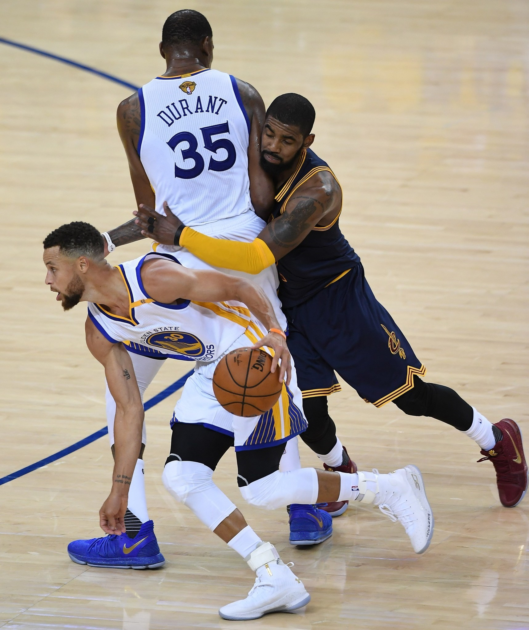 Kevin Durant #35 of the Golden State Warriors sets a pick on Kyrie Irving #2 of the Cleveland Cavaliers as teammate Stephen Curry #30 drives to the basket during the 2017 NBA Finals.